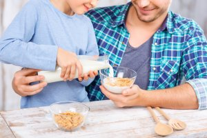 What milk is best for kids? Father and daughter pouring milk in cereal